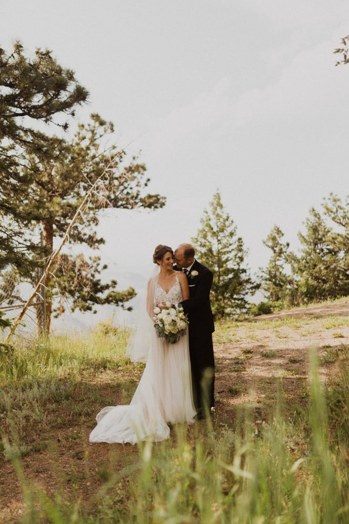 Bride and groom kissing on mountain in Colorado