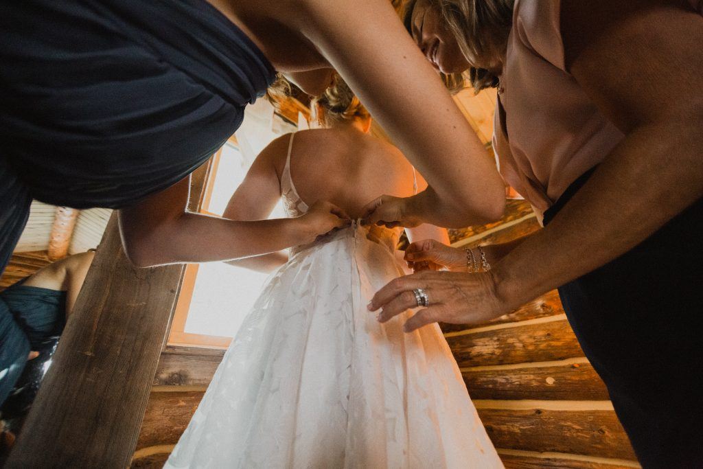 Bride getting her dress on before wedding in Colorado