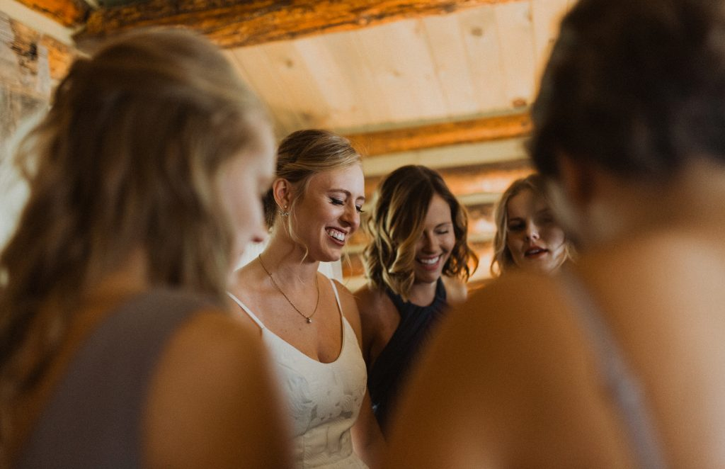 Bride and bridesmaids praying before ceremony in Granby, Colorado